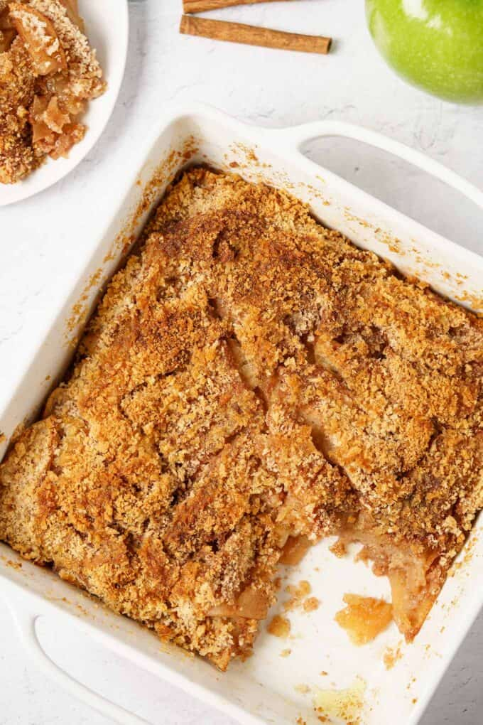 Apple brown betty in a square, white baking dish with one serving removed.