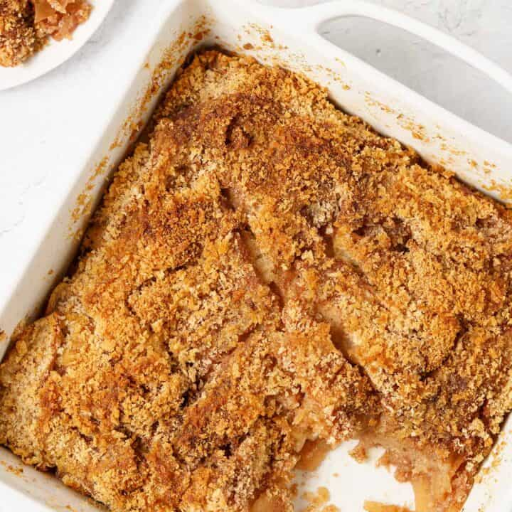 Apple brown betty in a baking dish with one serving removed.