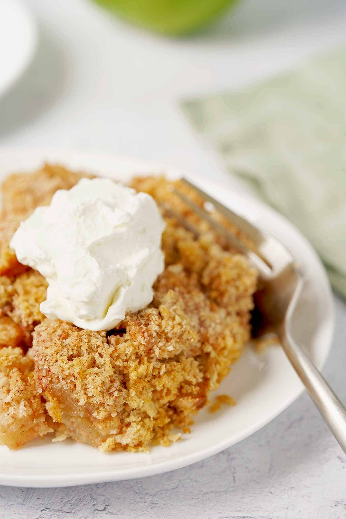 A serving of apple brown betty topped with whipped cream on a white plate.