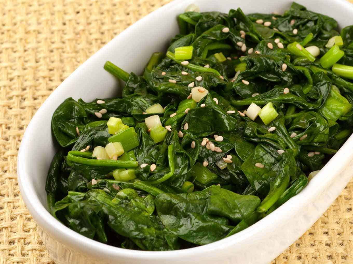 Serving dish of sautéed spinach topped with chopped scallions and sesame seeds.