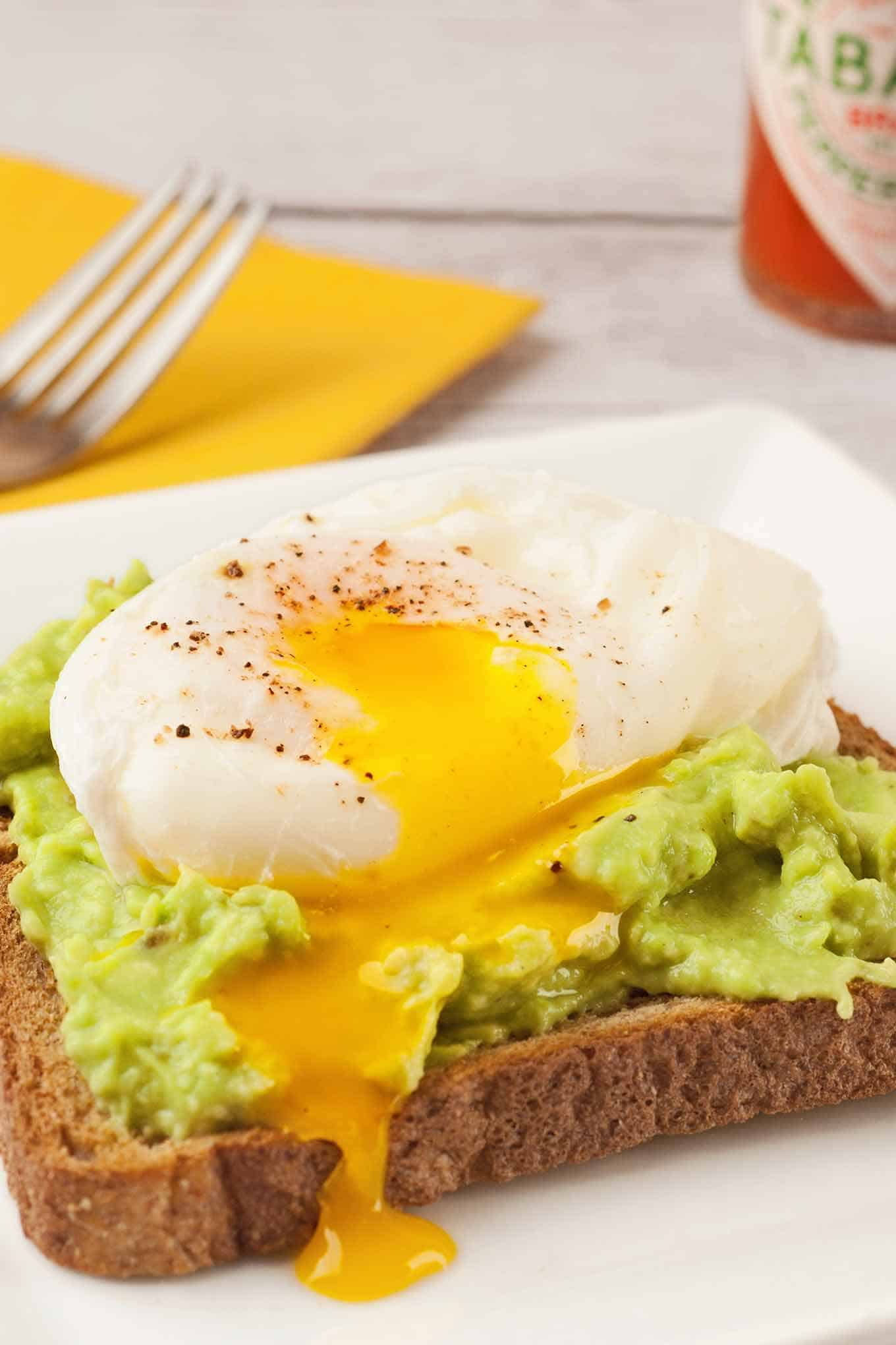 Plate of wheat toast topped with mashed avocado and a poached egg with Tabasco sauce in the background.