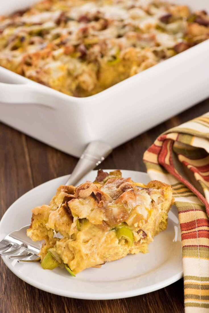 Good for brunch, lunch or a light weeknight dinner, this make-ahead strata combines toasted wheat English muffins, eggs, bacon, leeks and Gruyere cheese. #eggstrata #bacon #breakfast #brunch