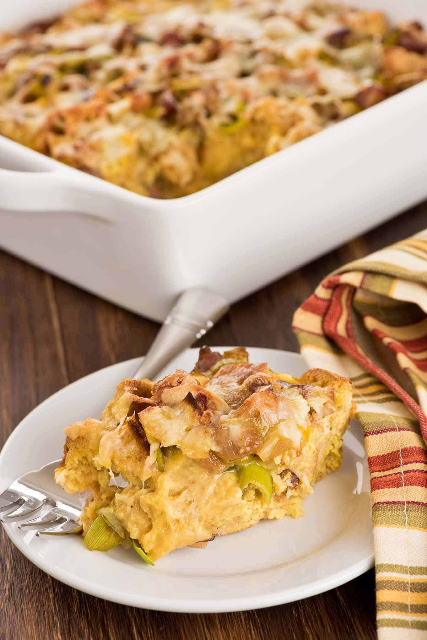 A serving of bacon, leek, and cheese strata on a plate with the casserole in the background.