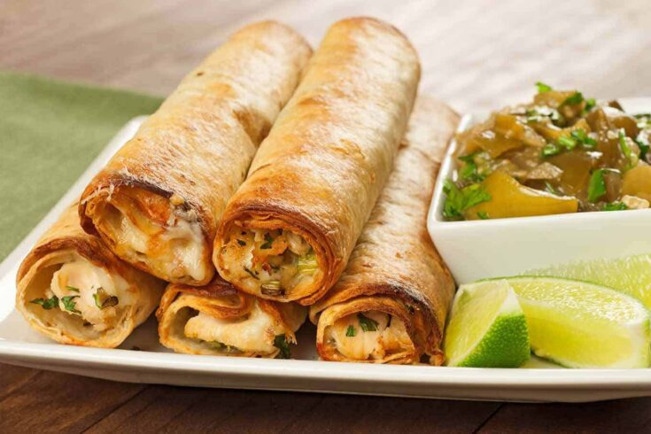 Served with a flavorful tomatillo sauce, these flautas are filled with chicken, Pepper Jack cheese, scallions, and cilantro and baked in the oven until crisp and lightly browned. #flautas #chickenflautas