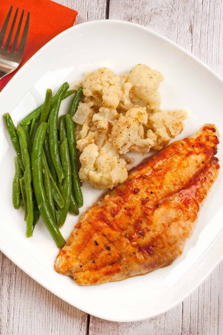 Flavored with a mixture of melted butter, tomato, and a spicy, Creole seasoning blend, these baked catfish fillets make a quick and easy dinner. #creolefood #bakedfish #catfish