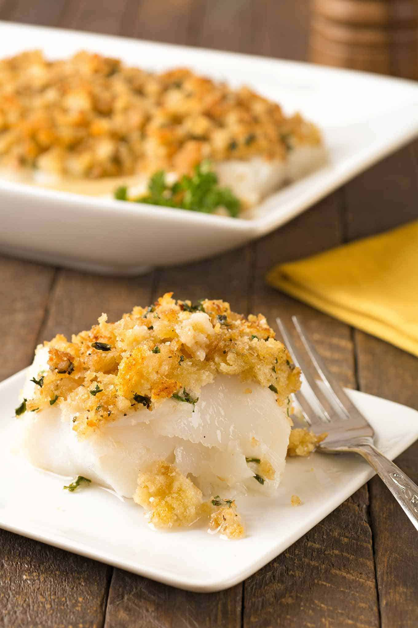 A serving of baked cod topped with a mixture of buttered crumbs, garlic, and parsley.
