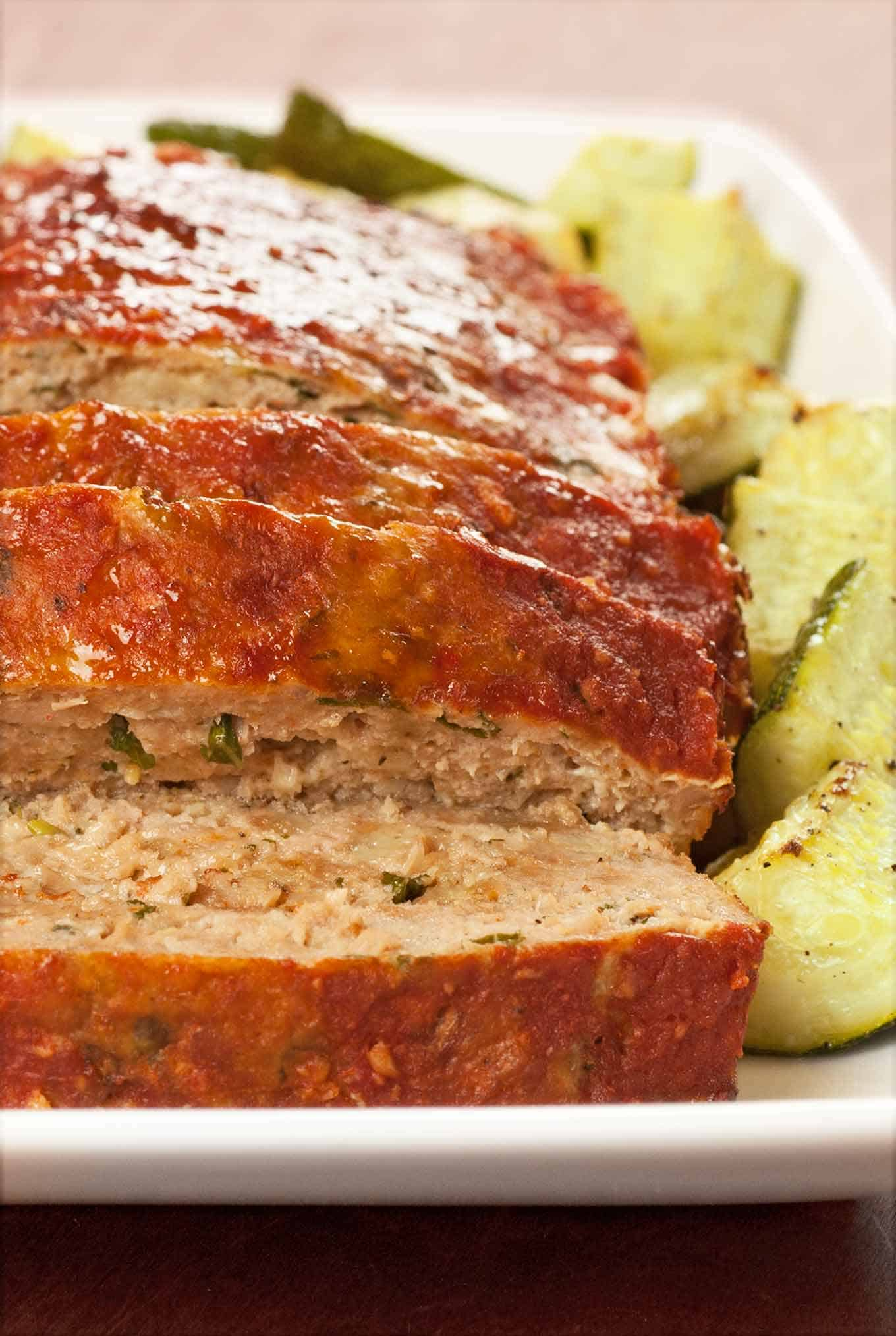 Sliced turkey meatloaf on a serving plate surrounded by roasted zucchini.