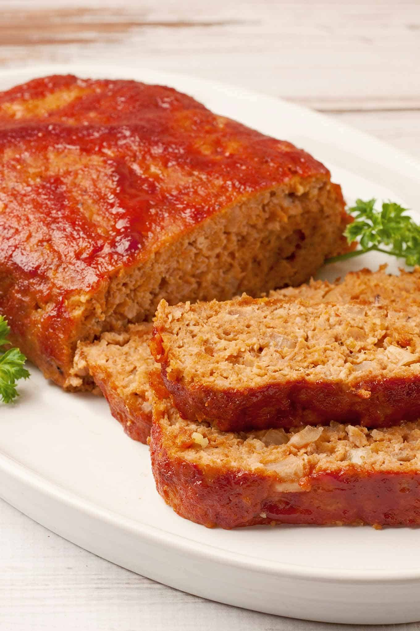 Barbecue chicken meatloaf on a serving plate with three slices cut from the end and parsley as garnish.