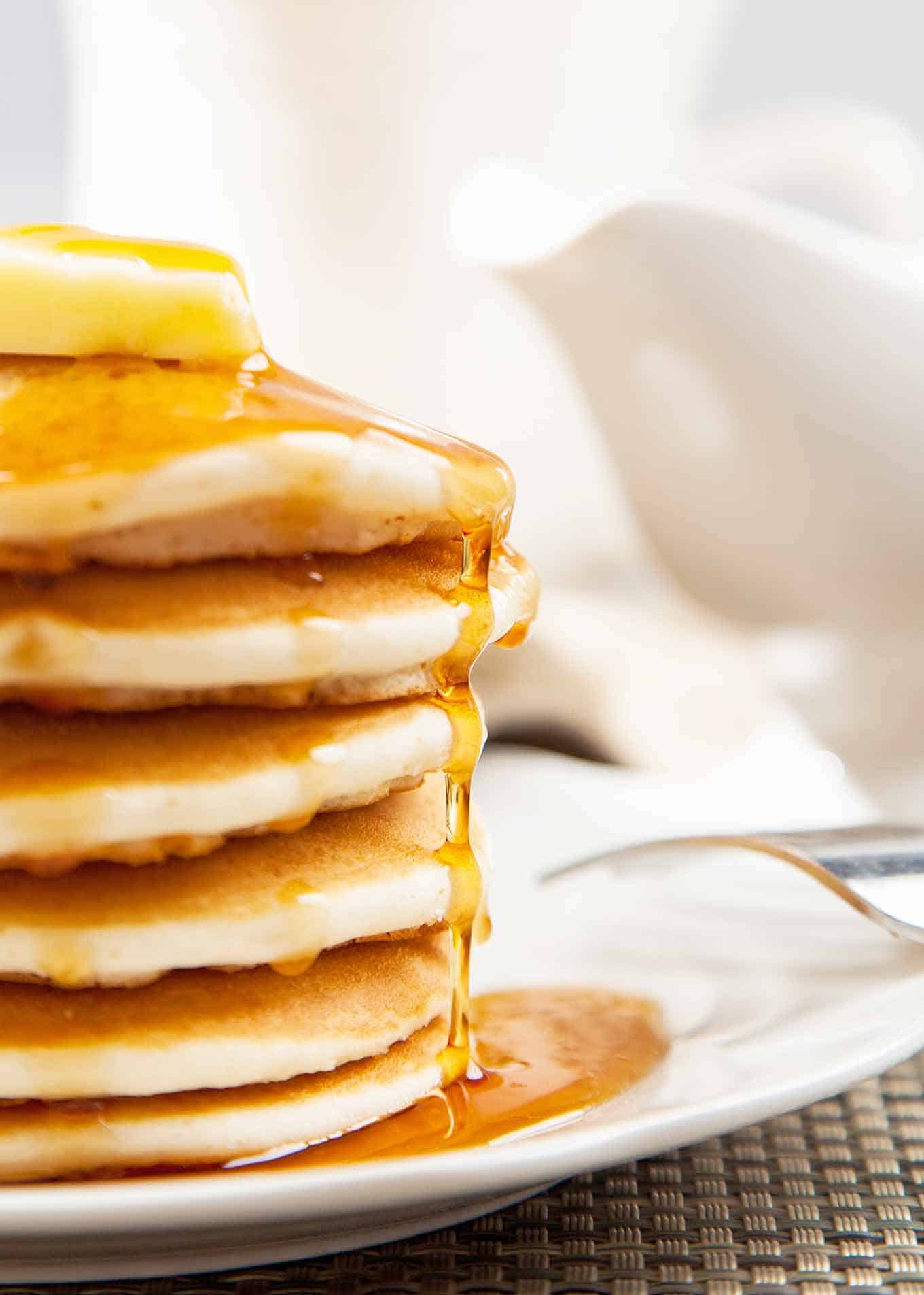 Stack of pancakes on a white plate topped with butter and syrup.