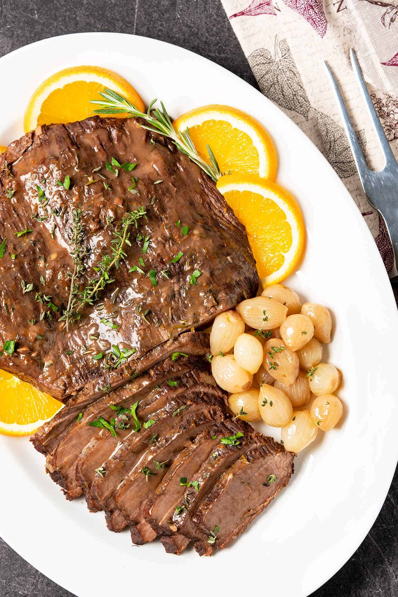 Platter of carved beef brisket garnished with oranges, pearl onions, fresh rosemary and thyme.