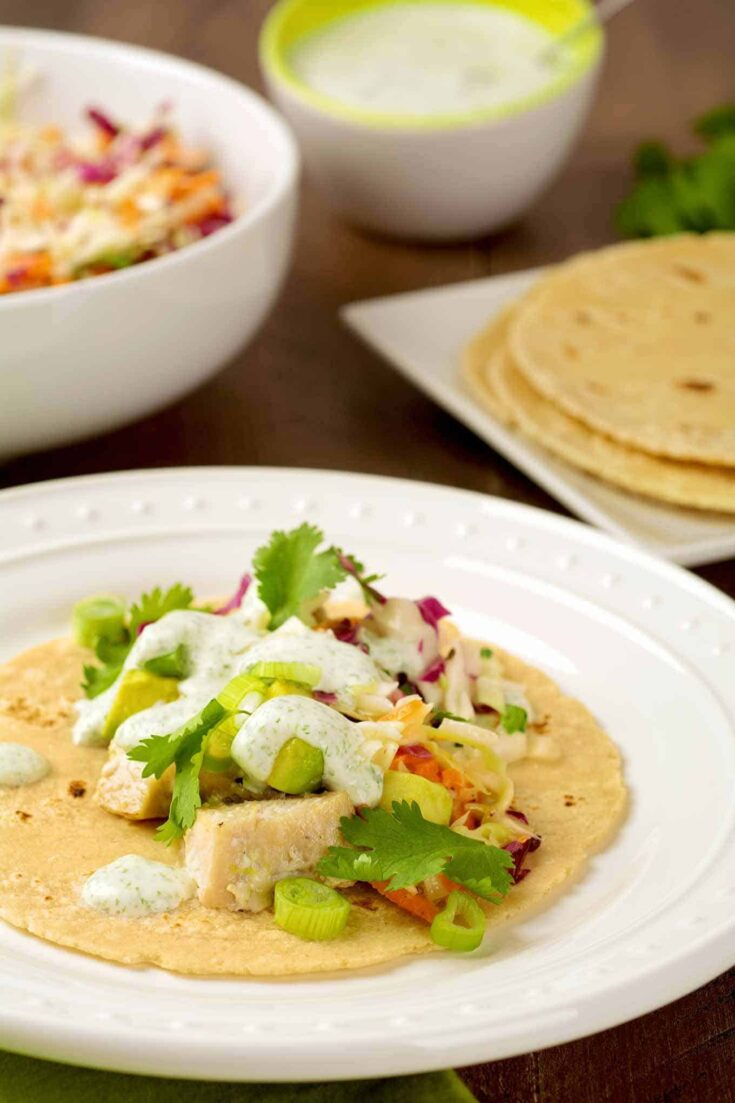 Filled with tender chunks of mahi mahi, avocado, homemade slaw and a creamy cilantro-lime dressing, these easy broiled fish tacos make a light, delicious dinner. #fishtacos #mexicanfood