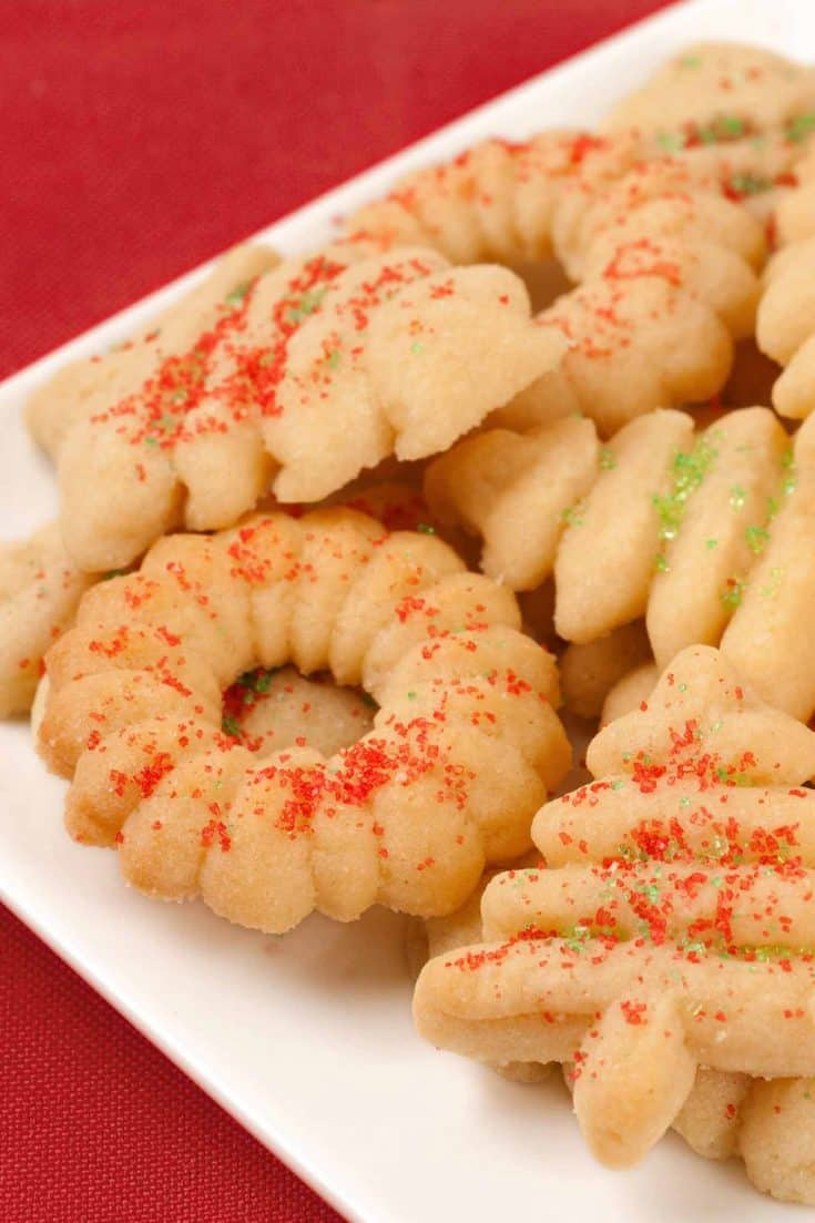 Rich, buttery spritz cookies are a classic favorite, and with the help of cookie press, you can easily make a big batch for gift giving and entertaining. #spritzcookies #christmascookies #buttercookies #cookiepresscookies