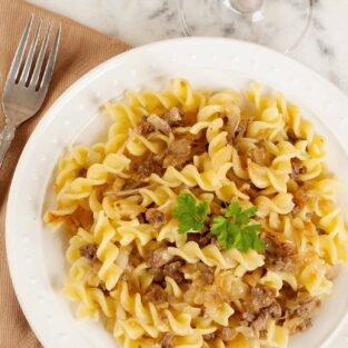 A single plated serving of rotini pasta with crumbled Italian sausage and caramelized onions.