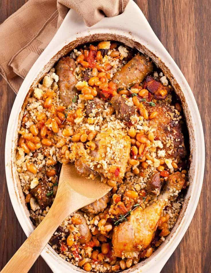 Flavored with garlic, white wine and thyme, our version of this classic French casserole is made with chicken legs, cubed pork, white beans and sausage. #cassouletrecipe #easycassouletrecipe #frenchfood