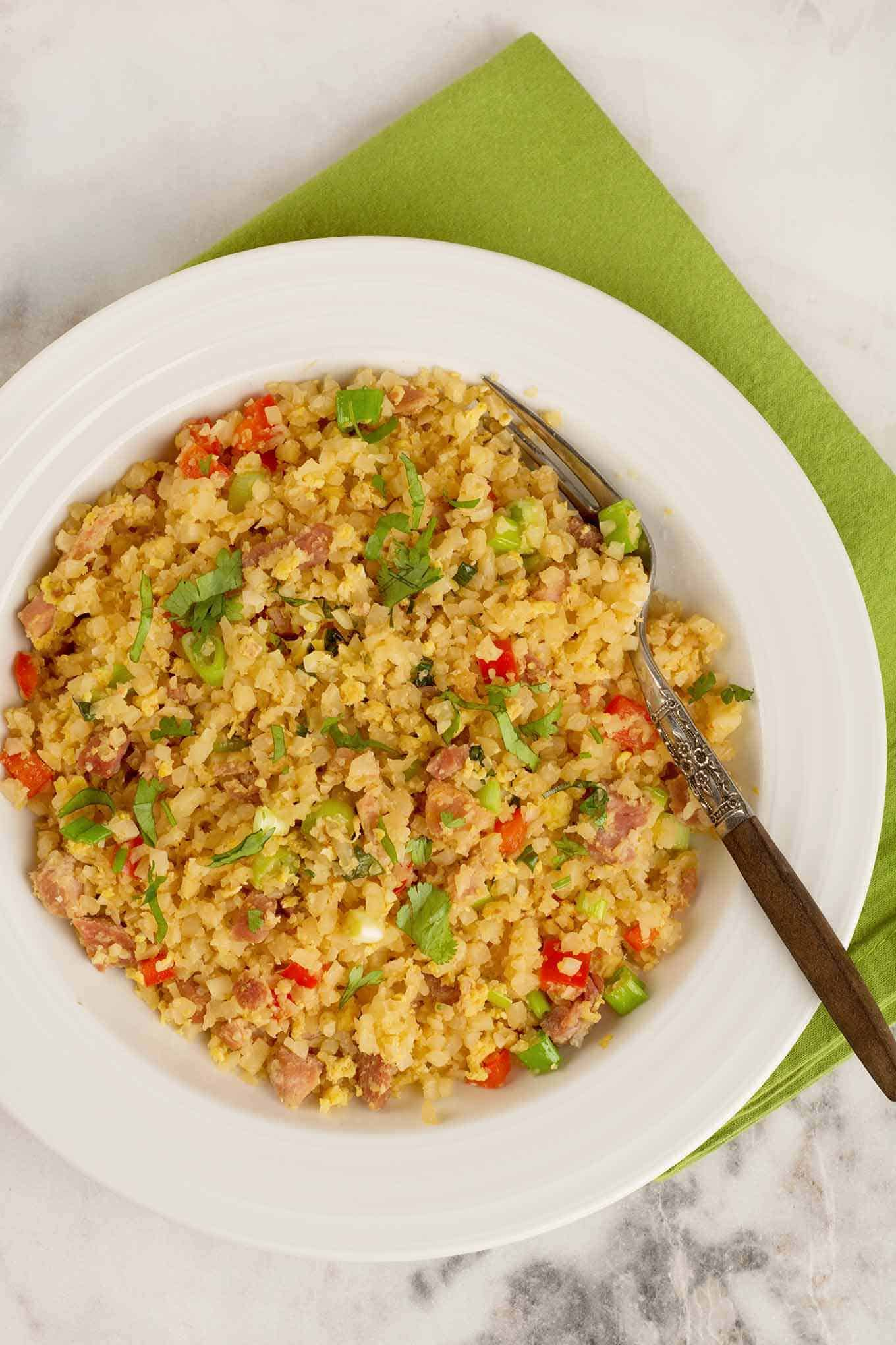 A single serving of cauliflower fried rice garnished with chopped cilantro and scallions