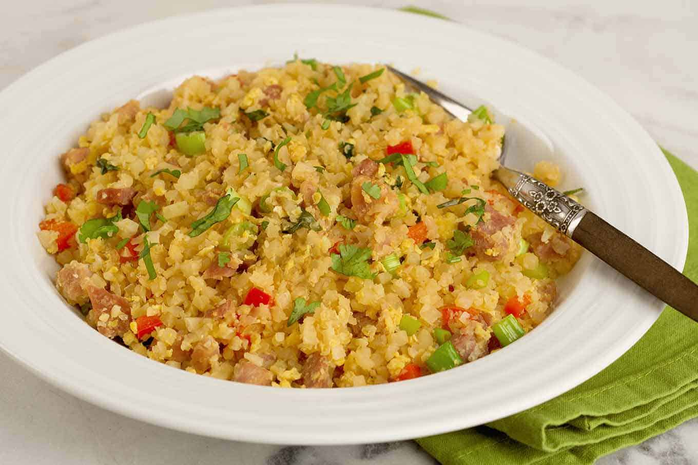 A serving of riced cauliflower fried rice in a shallow bowl with fork.