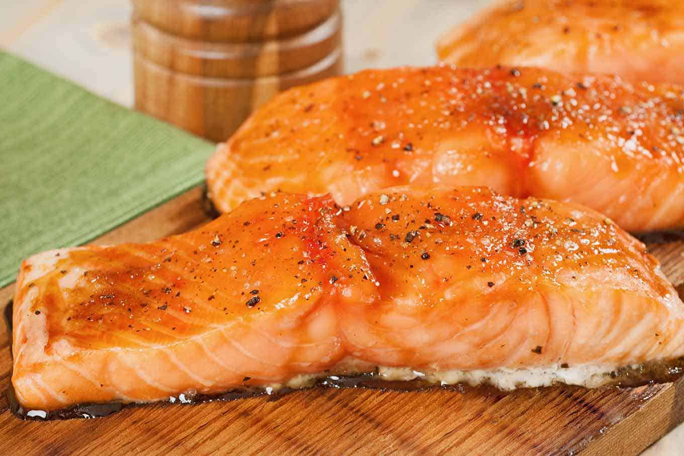 A side view of two salmon fillets that have been seasoned and grilled on a cedar plank.