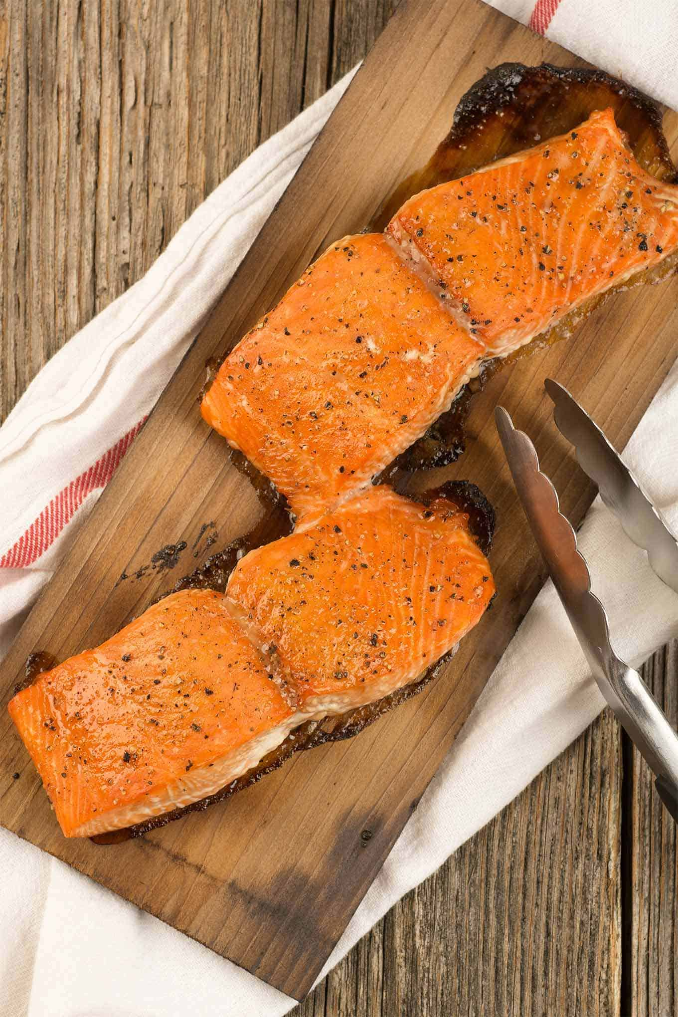 Two grilled salmon fillets on a cedar plank with grilling tongs.