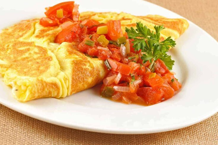 Chopped tomatoes and scallions cooked in butter makes a delicious topping for these cottage cheese and parsley-filled omelets. #breakfast #brunch #omelet