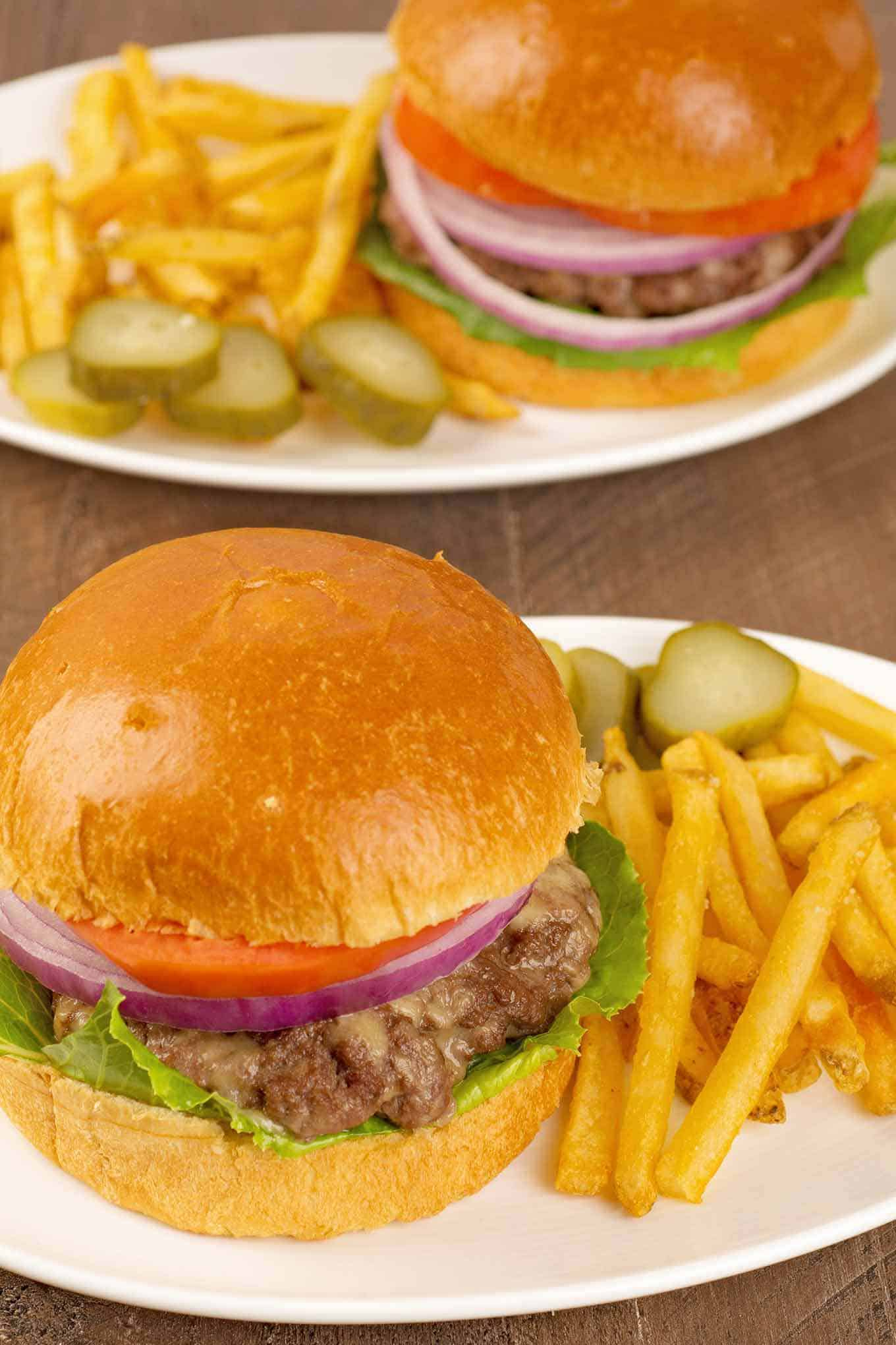 Two plated servings of burgers and fries.