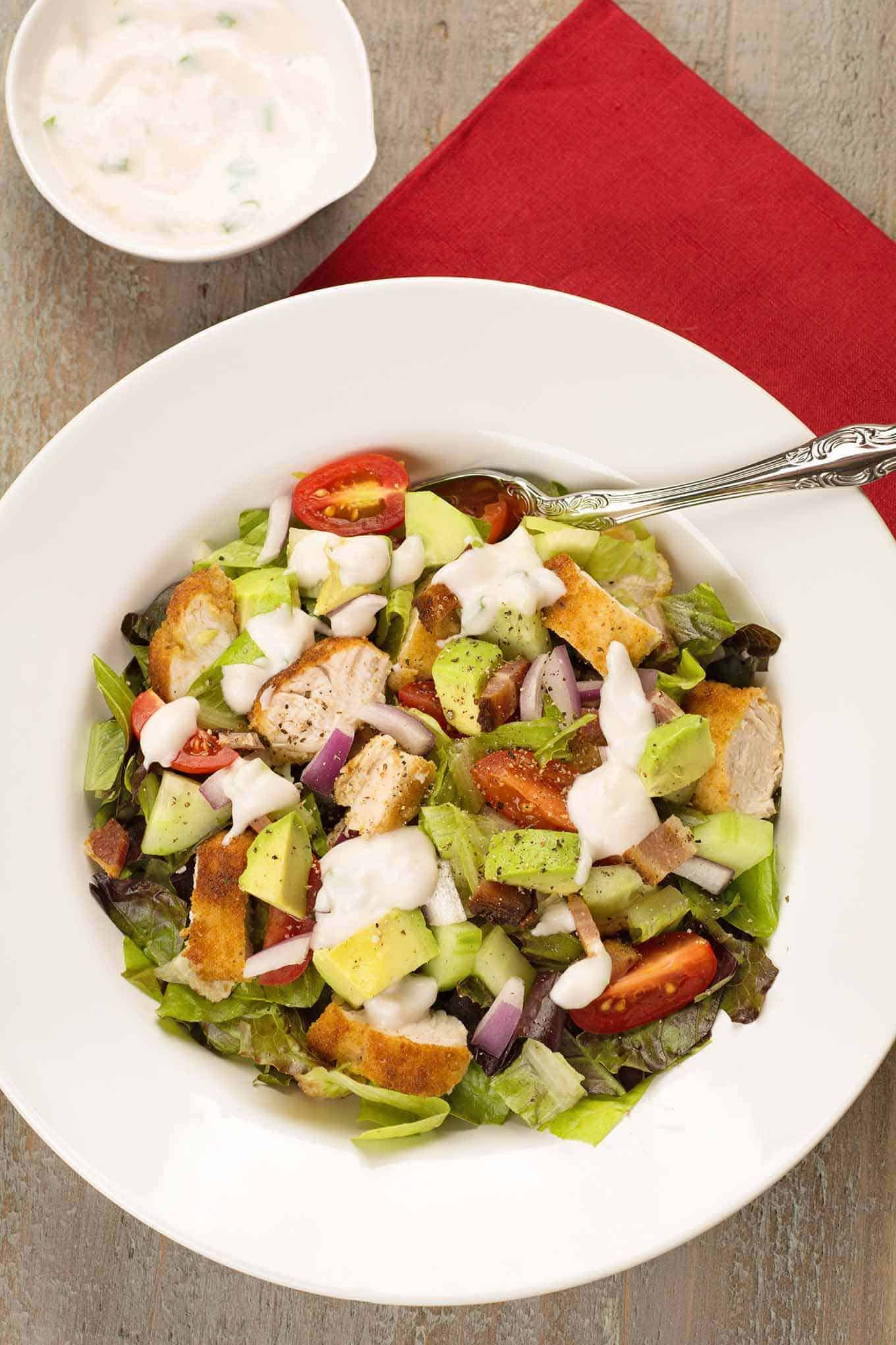 A serving of chopped greens and diced chicken tenderloins, avocado, grape tomatoes, red onion, and bacon topped with ranch dressing.