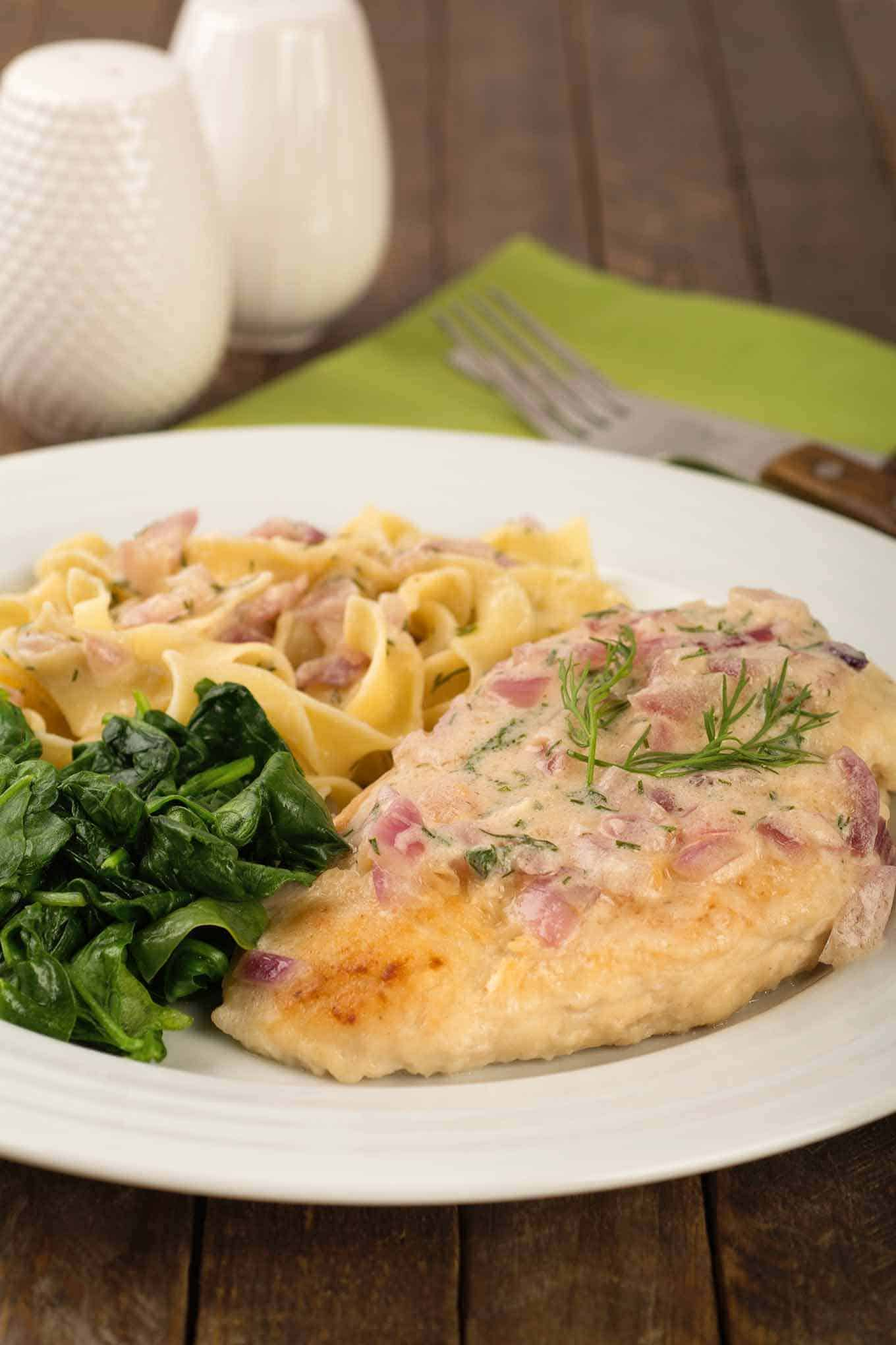 Chicken breast with onion and dill sauce on a plate with egg noodles and spinach.