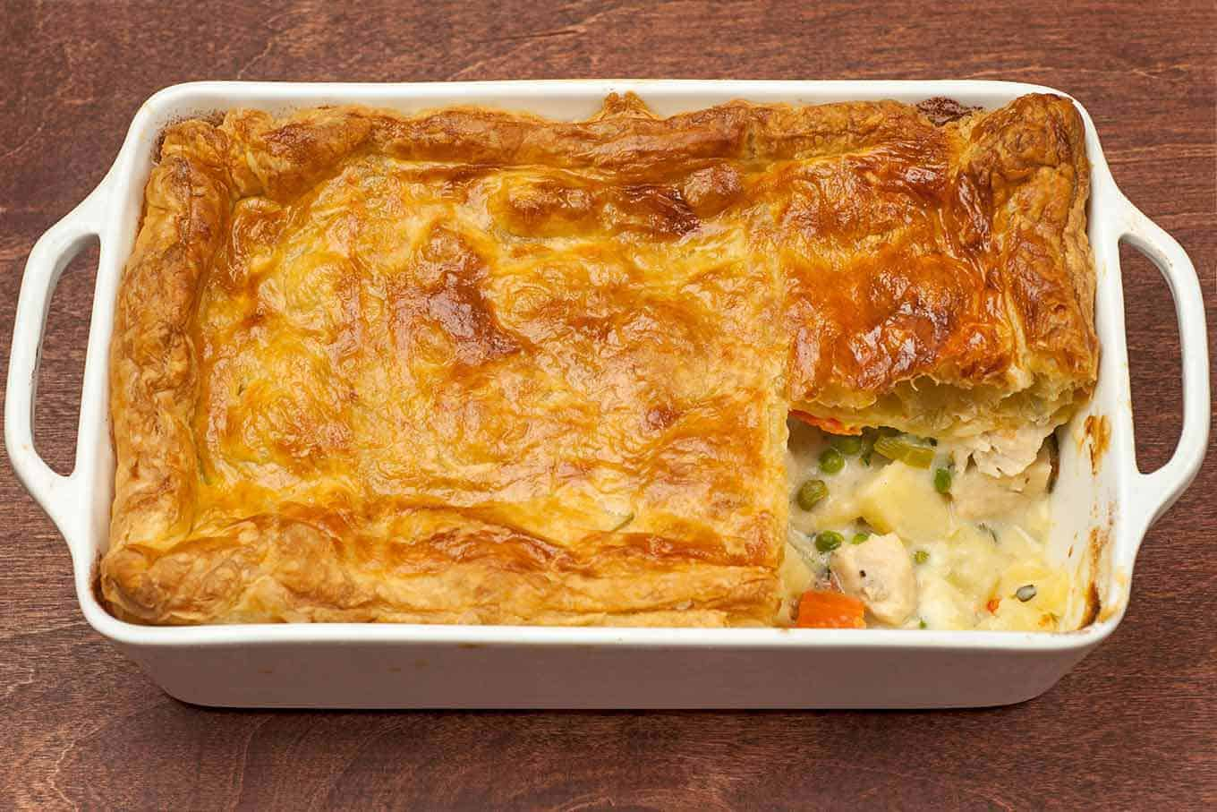 Chicken pot pie topped with puff pastry in a baking dish