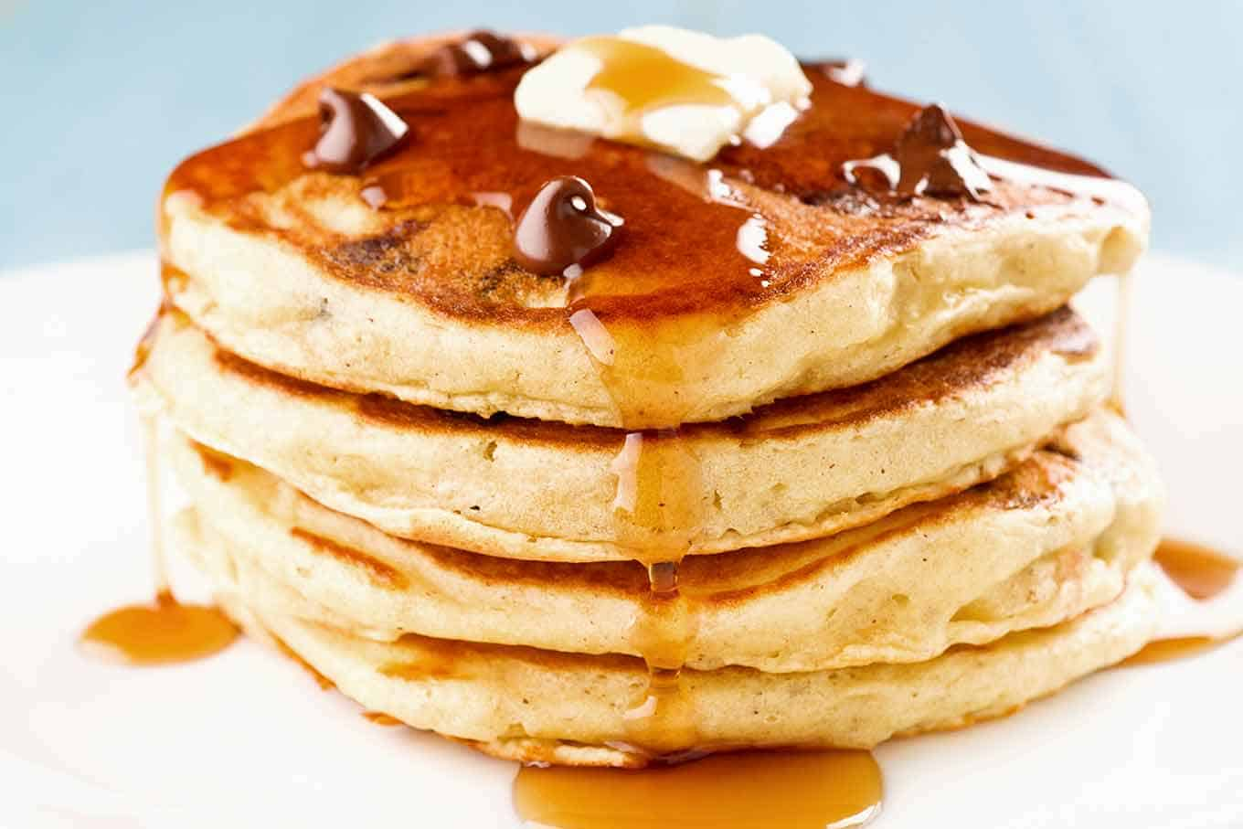 A serving of chocolate chip pancakes on a plate topped with a pat of butter and a drizzle of syrup.
