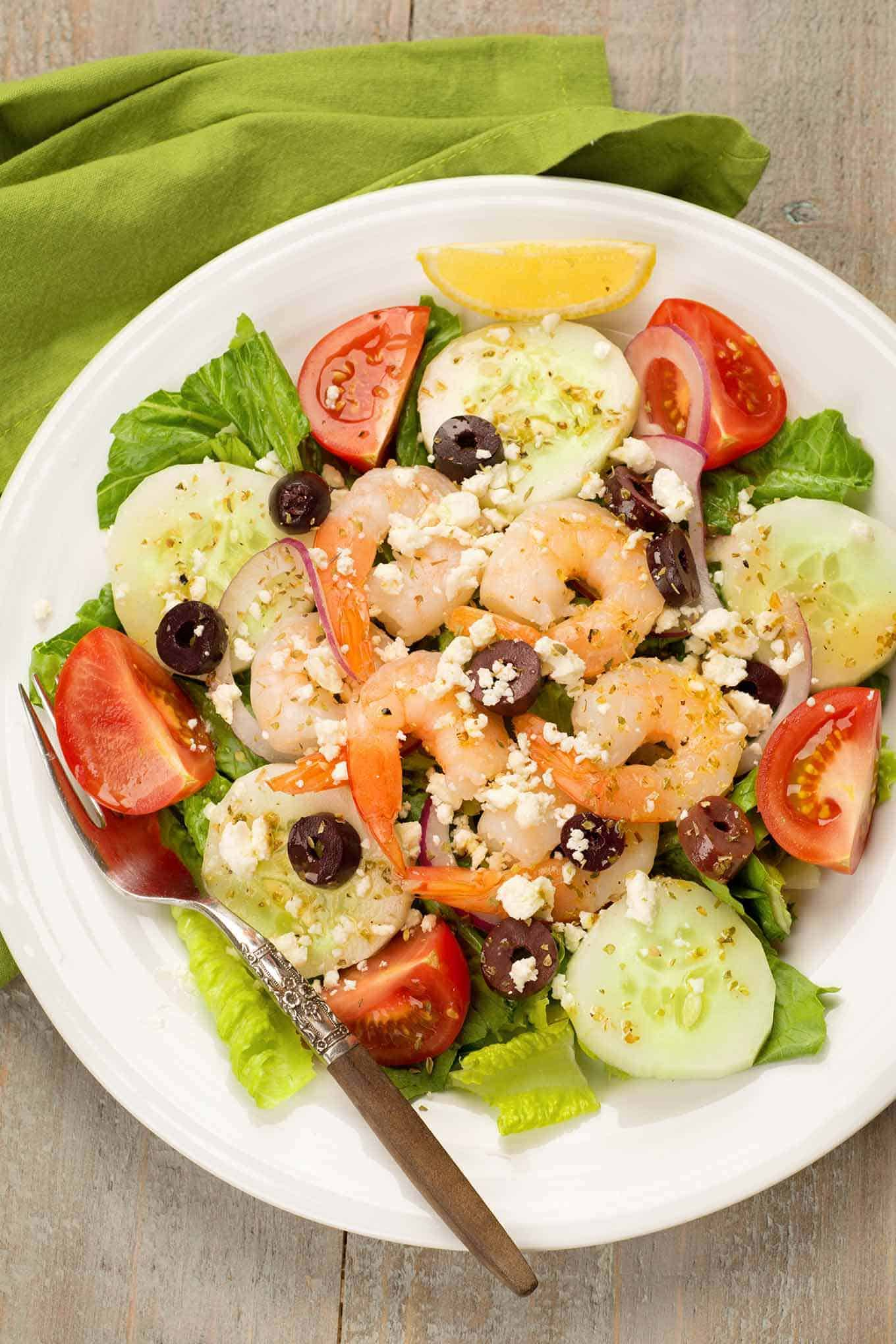 A serving of Greek salad with shrimp topped with crumbled feta cheese and Kalamata olives.