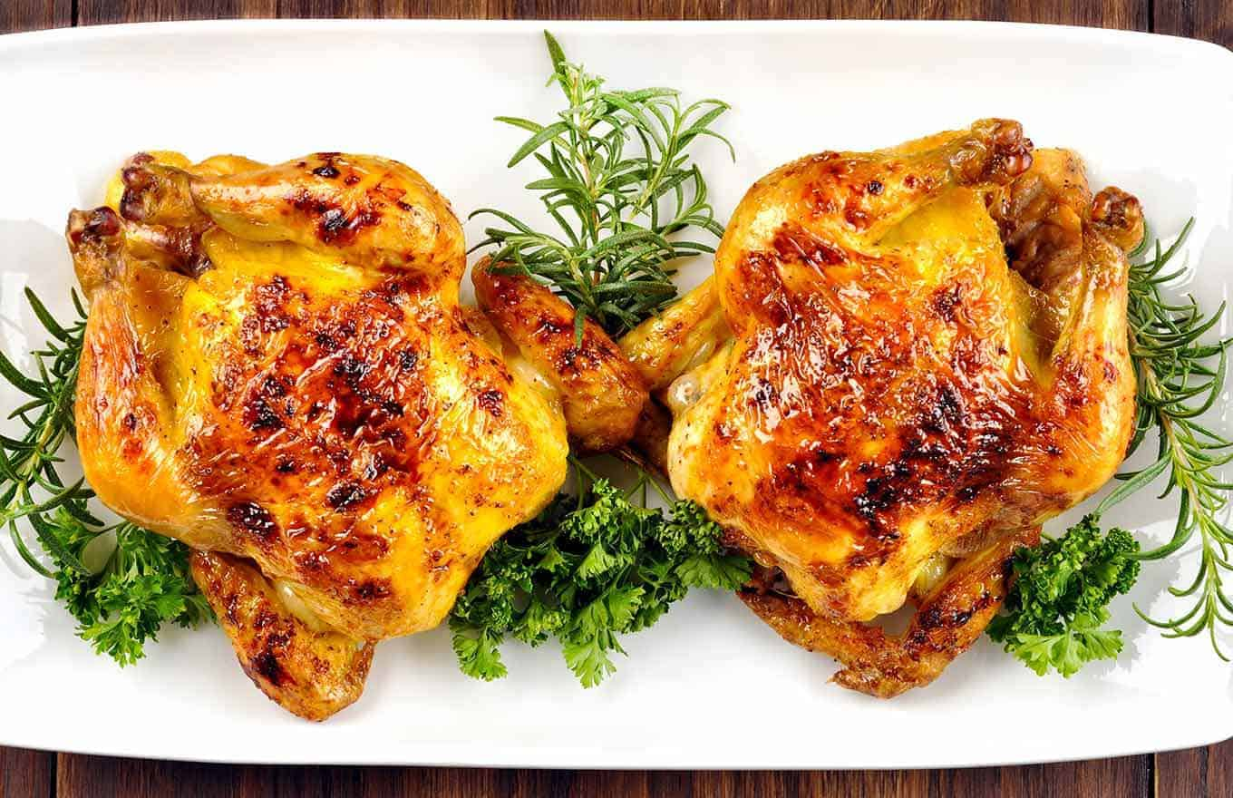Overview of bourbon-glazed Cornish hens on a serving platter with parsley and rosemary garnish.