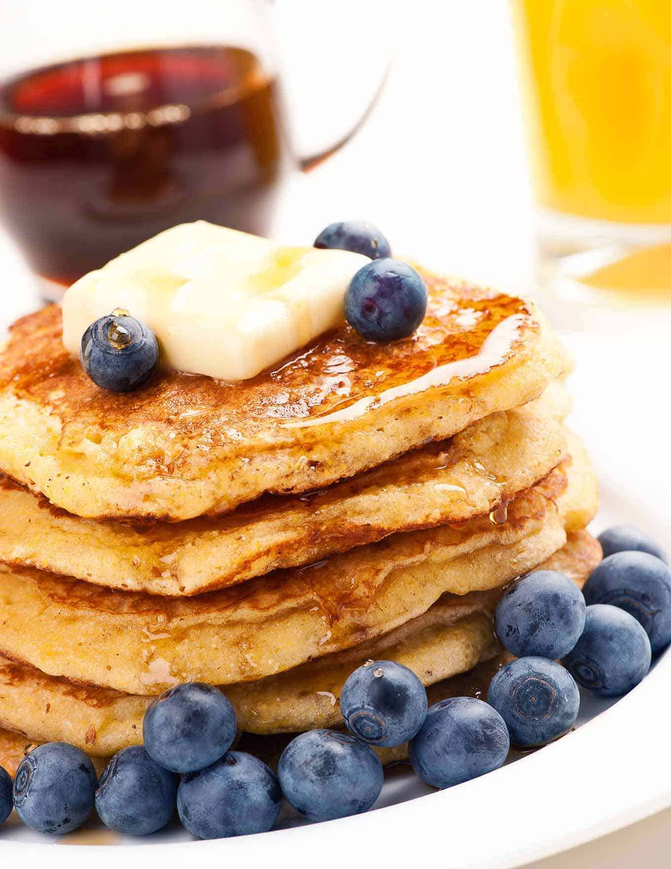 A stack of cornmeal pancakes on a plate topped with a pat of butter, maple syrup and fresh blueberries.