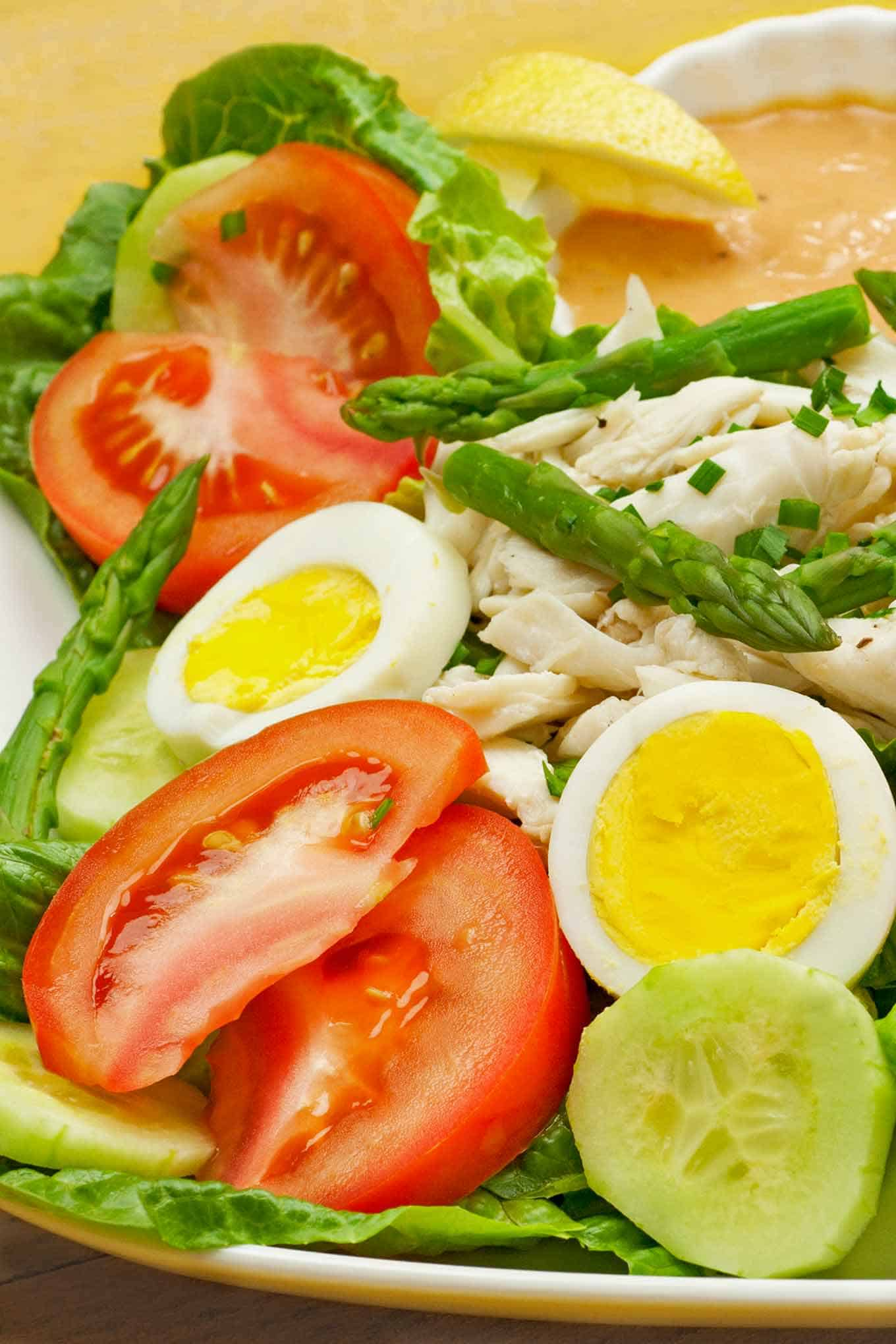 Crab Louie salad on a plate, lettuce, tomato, cucumber, hard cooked eggs, asparagus, lump crab meat, dressing, and a lemon wedge.