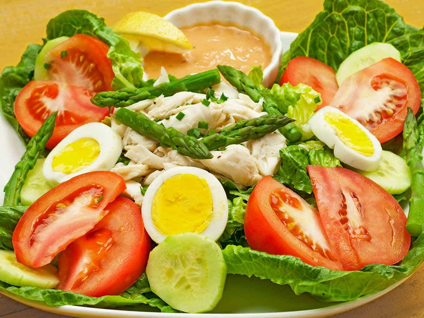 A serving of crab Louie salad, lettuce, tomatoes, hard cooked eggs, crab, cucumber, asparagus, dressing, and a lemon wedge.