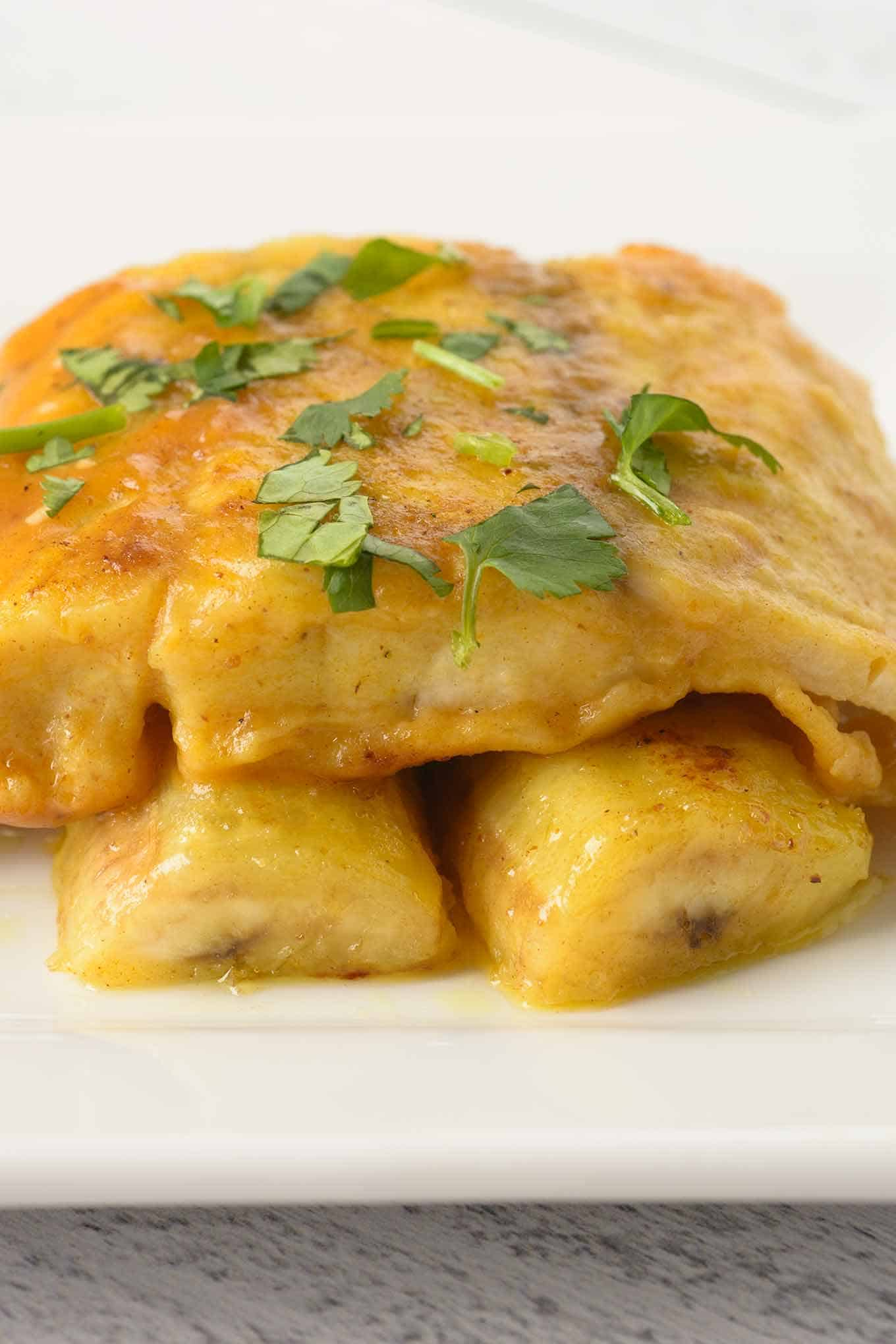A single serving of a pan-fried fish fillet and sliced bananas coated in a light curry sauce.