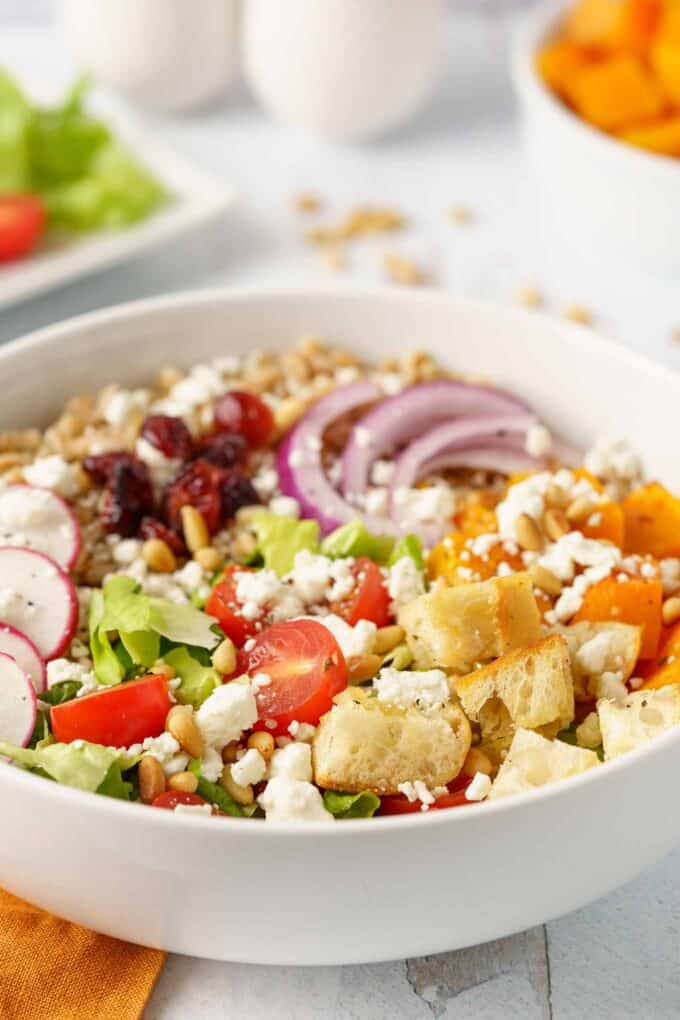 Individual portion of farro salad in a bowl including croutons, cherry tomatoes, salad greens, and other toppings