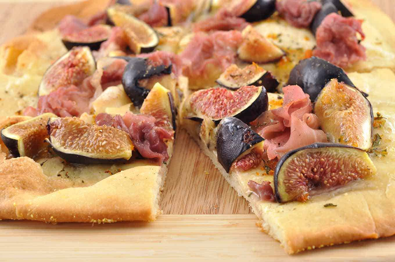 Squares of flatbread topped with fresh figs, Brie cheese and prosciutto ham on a wooden cutting board