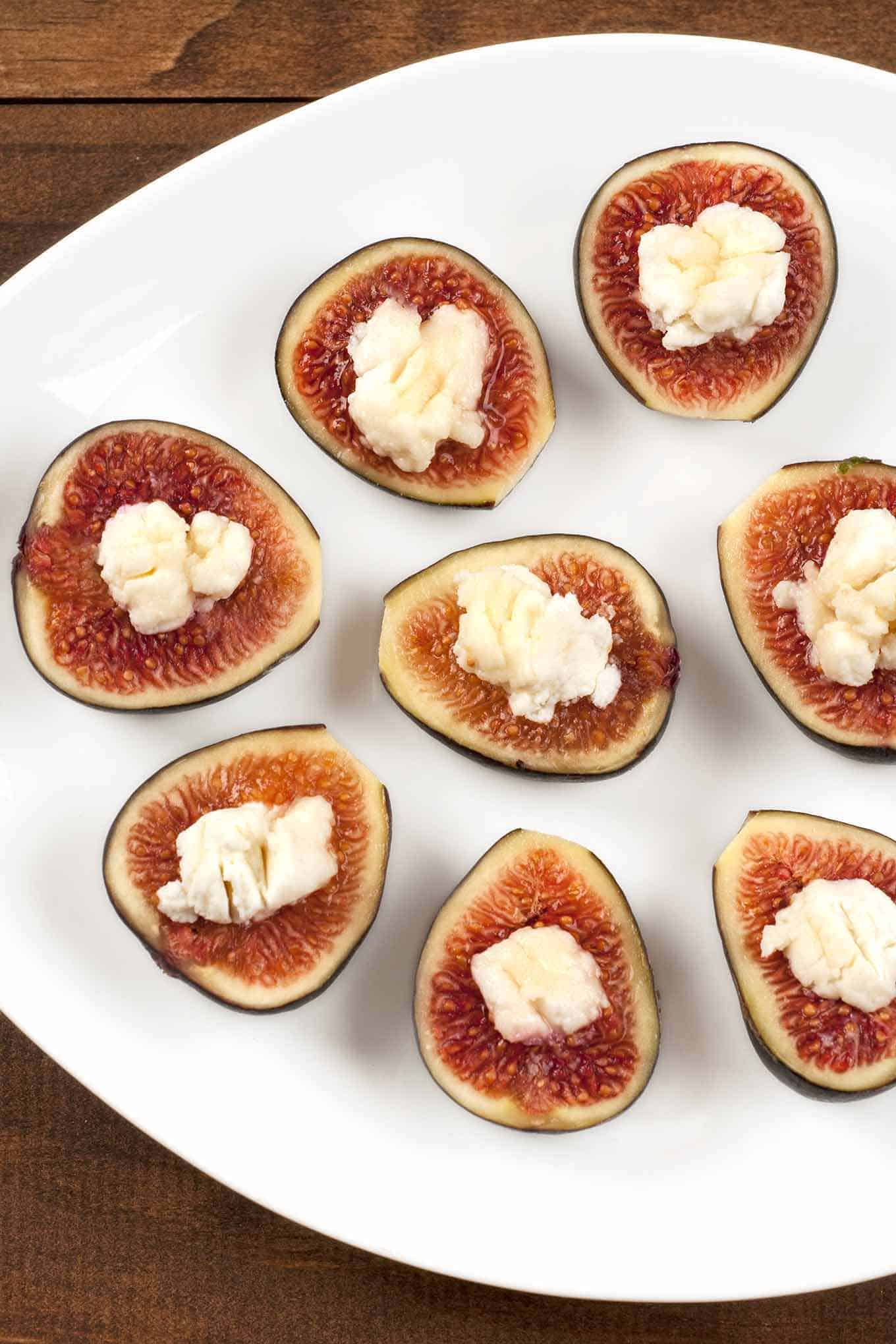 A platter of fresh fig halves topped with crumbled goat cheese and drizzled with honey.