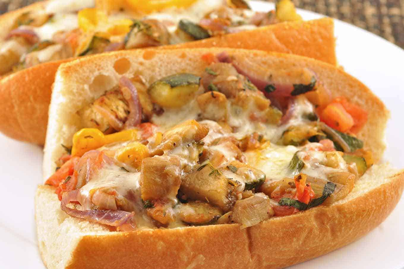 Toasted baguette filled with eggplant, bell peppers, zucchini, and melted cheese on a plate.