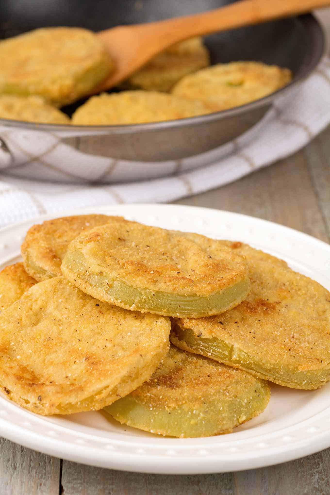 A plate stacked with fried green tomatoes with a frying pan filled with more in the background.
