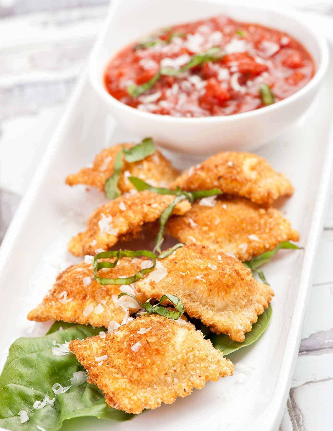 Fried ravioli on serving plate with marinara dipping sauce