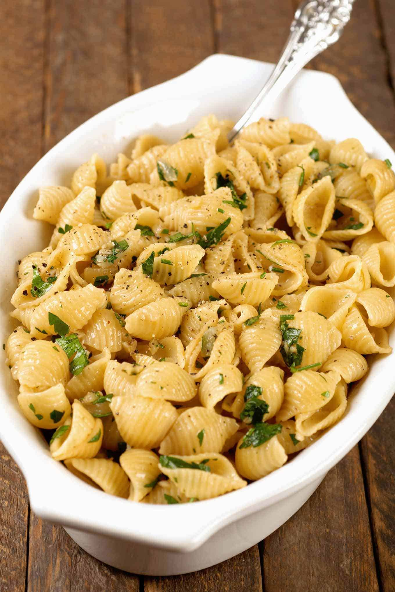 Serving dish filled with pasta shells in garlic butter garnished with parsley and cracked black pepper.