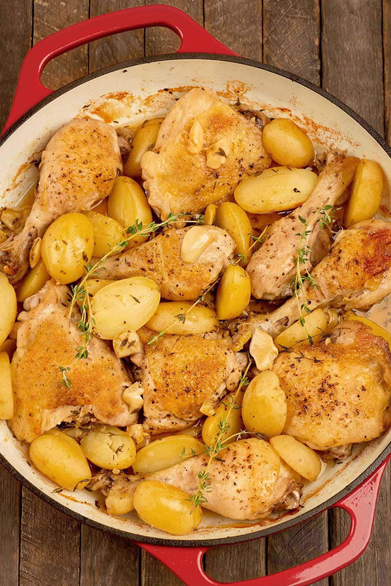 A cast iron skillet filled with roasted chicken thighs and drumsticks, potatoes, garlic, and sprigs of fresh thyme.