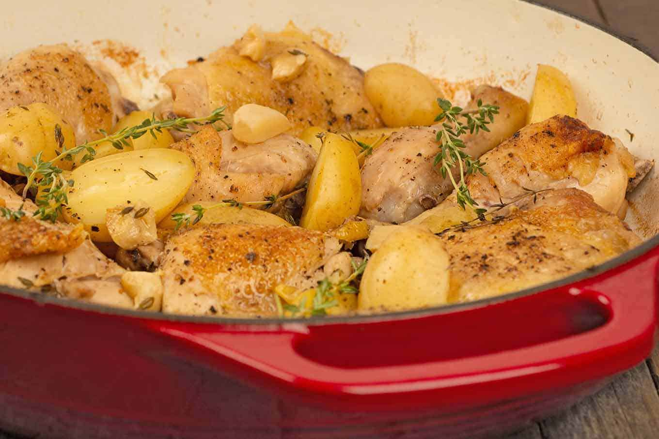 Side view of a red enameled cast iron pan filled with roasted chicken, whole garlic cloves, halved baby potatoes, and thyme.
