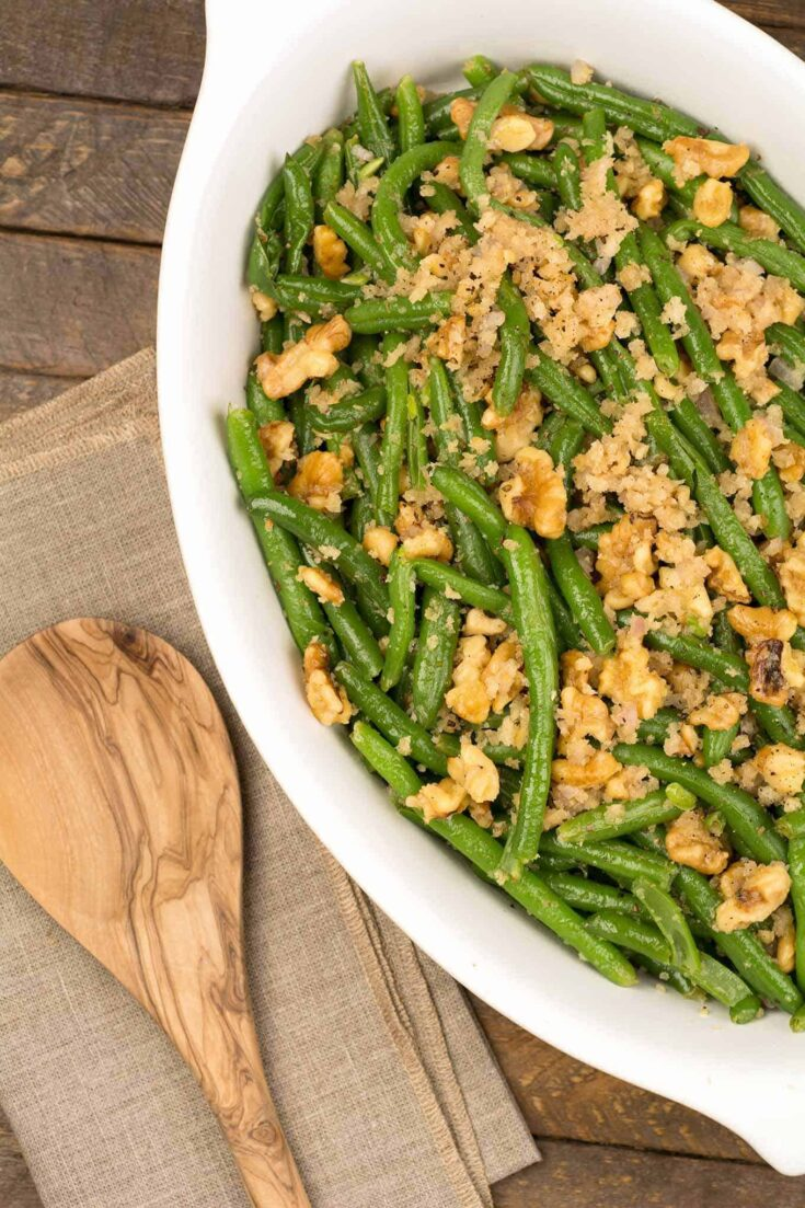 Oven-roasting green beans gives them a slight sweetness that pairs perfectly with the sautéed shallots and toasted walnuts in this versatile side dish. #greenbeanrecipes #greenbeancasserole #greenbeans