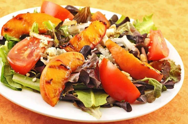 This colorful, composed salad includes field greens, tomatoes, onion, crumbled blue cheese, grilled peaches and a balsamic-honey vinaigrette. #grilledpeaches #peachsalad #saladrecipes
