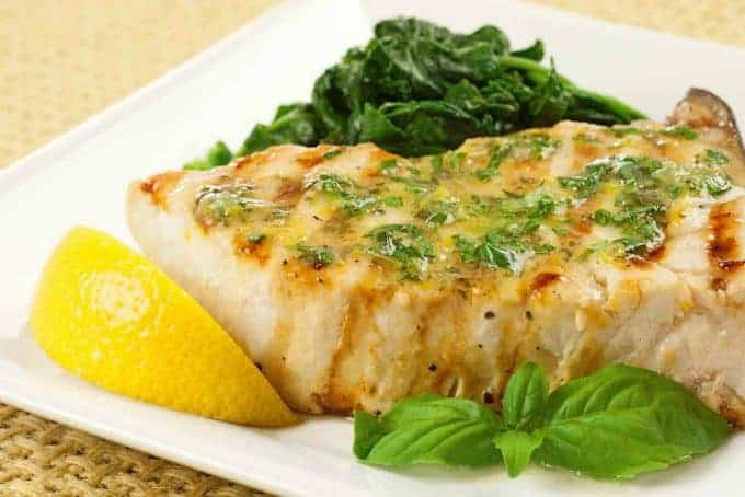 Plated serving of grilled swordfish with lemon basil butter.