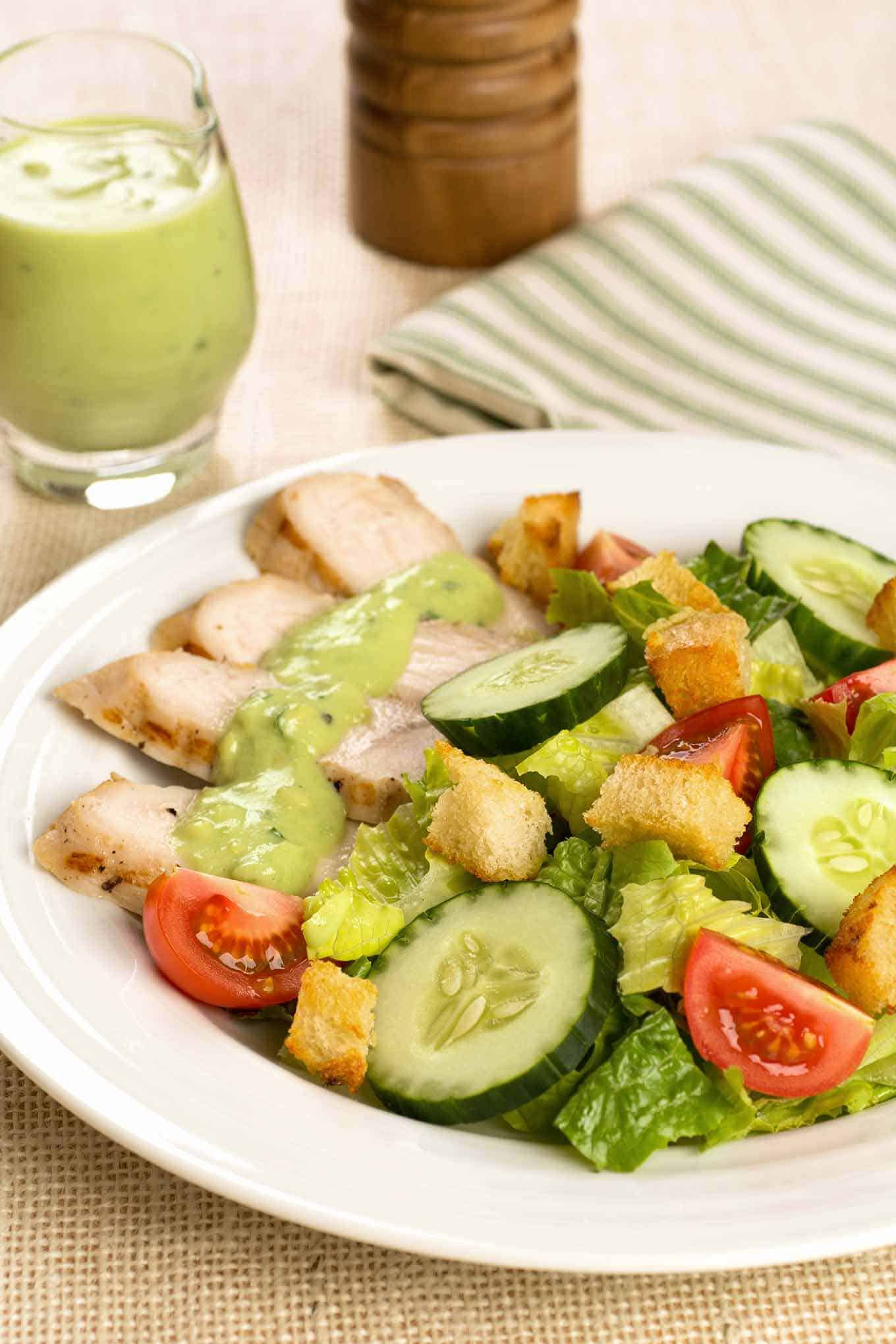 Serving of salad with grilled, brined turkey slices and a topping of avocado dressing.