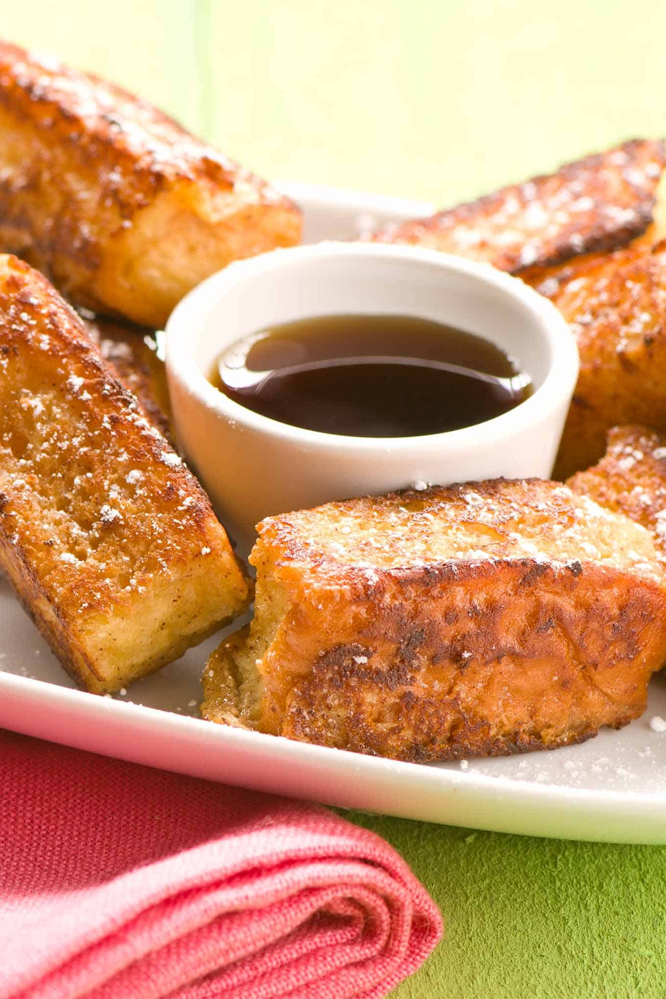 Single serving of Hawaiian French toast sticks with maple syrup.