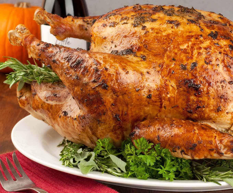 Uncarved herb roasted turkey on serving platter with fresh herb garnish