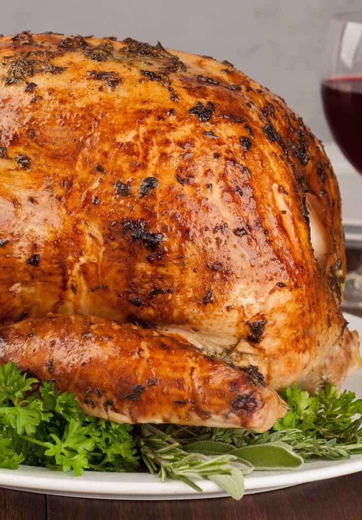 Our Herb Roasted Turkey recipe uses a coating of mayonnaise and chopped fresh herbs to add flavor, brown more evenly and keep the meat moist and juicy. #roastturkey #mayonnaisecoatedturkey #thanksgivingturkey #thanksgivingdinner #turkeyrecipes #turkey